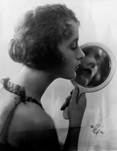 A woman looks at her reflection in the mirror
