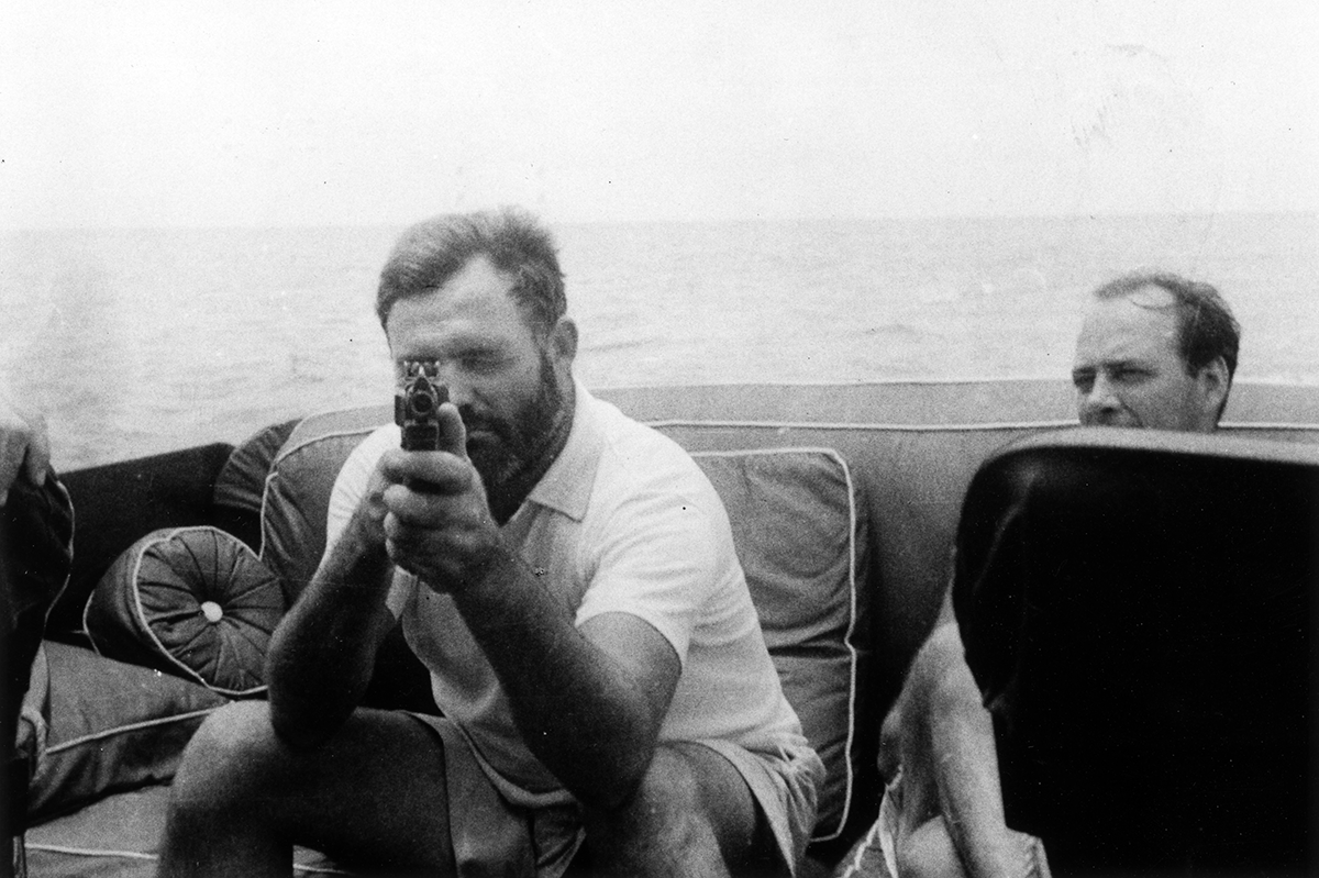 Black and white image of Hemingway sitting on a boat while holding a gun aimed at the camera