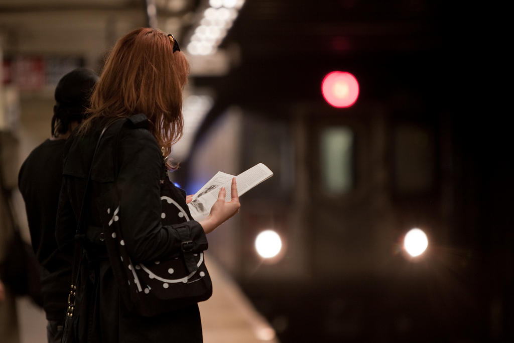 Image of a woman reading a book while waiting for the subway