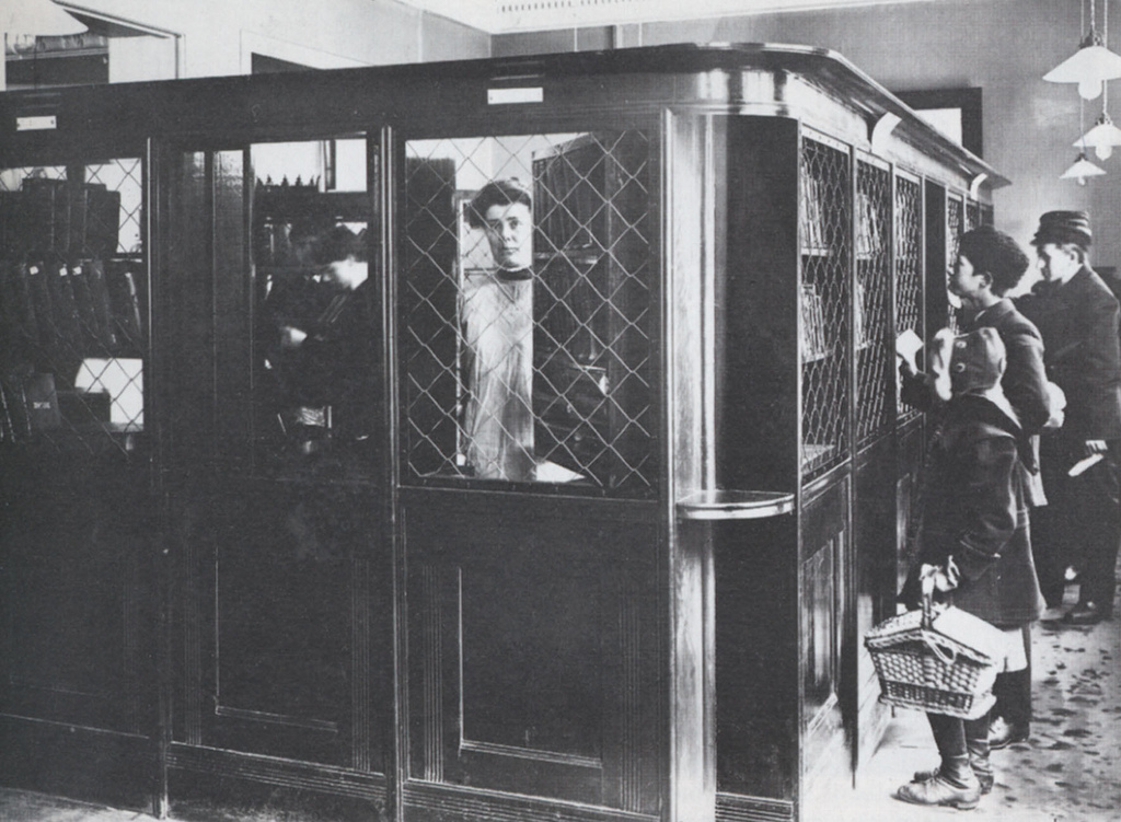 Black and white photo of a man inside an old mail room with people standing outside