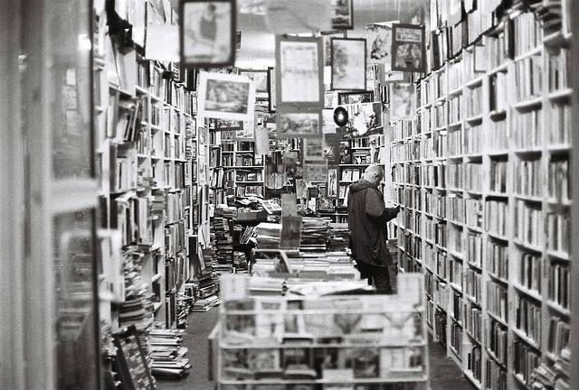 Black and white image of a man alone in an overstocked bookshop with piles of books on the ground