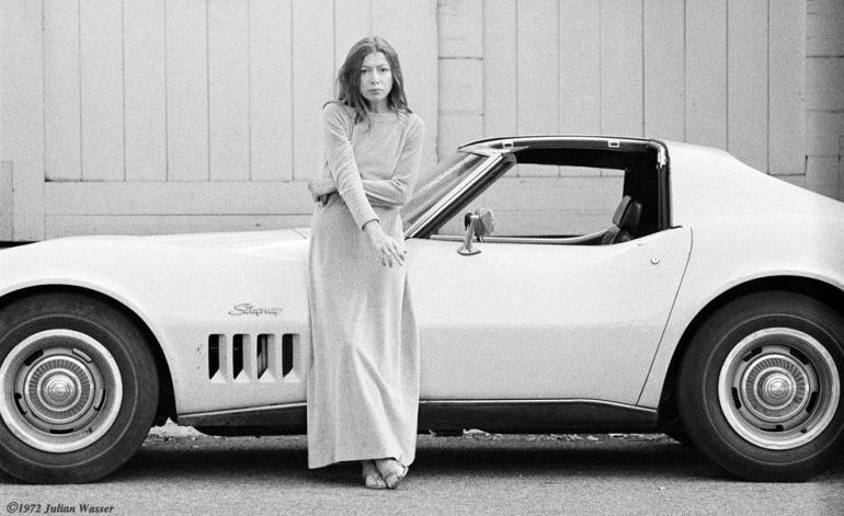 Black and white image of a woman in a long sleeve, floor length dress smoking a cigarette and leaning against an old white sports car