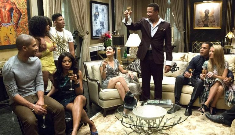 A still from the TV show Empire, showing the cast in a lavish living room as one character makes a toast