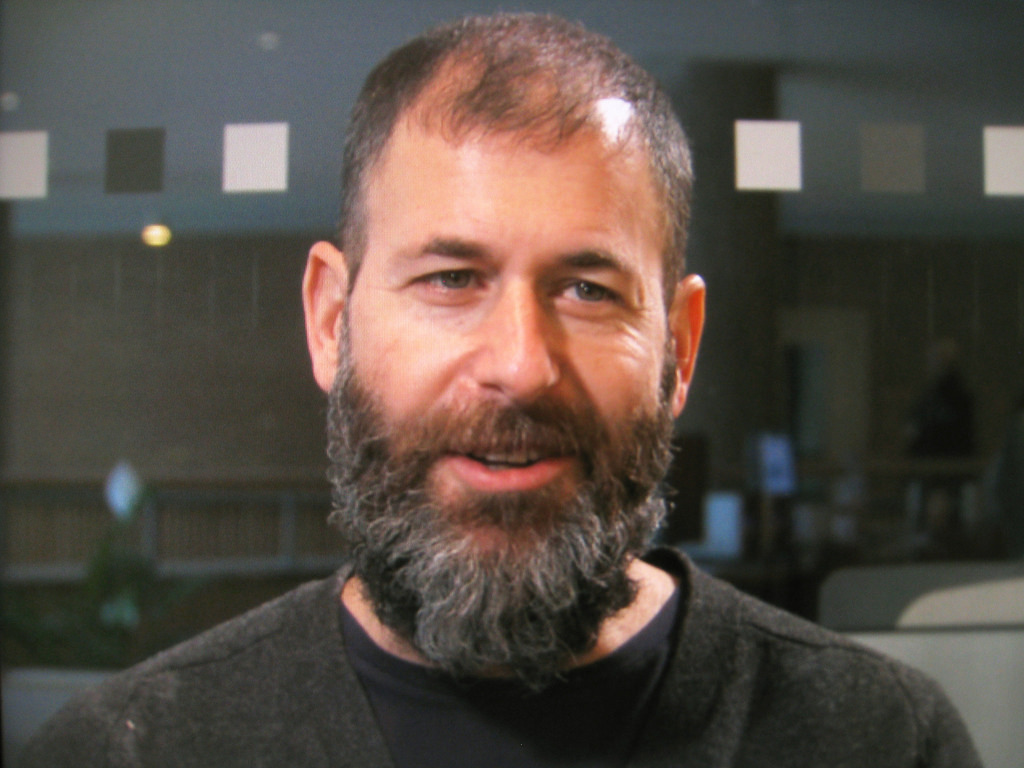 Photo of a white man with short hair and a long, dark grey beard