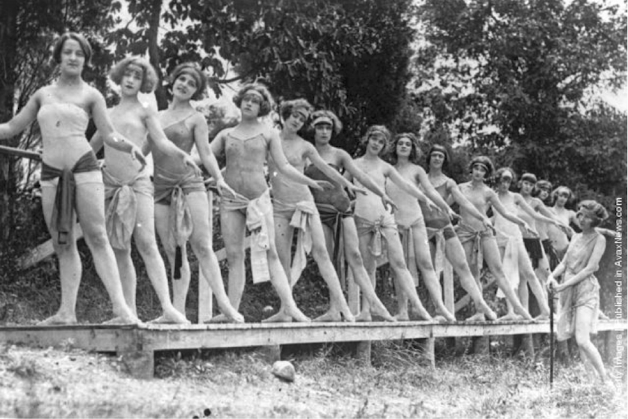Black and white photo of women wearing leotards on a dock outside, practicing barre exercises for ballet