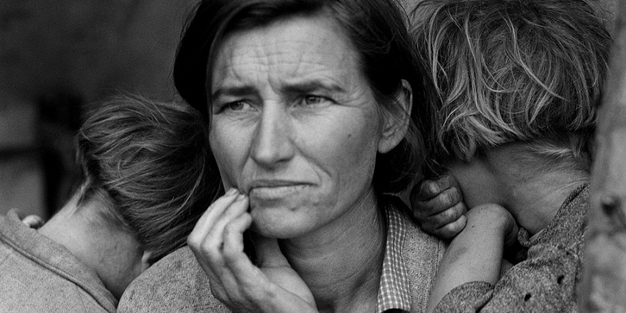 Black and white photo of a mother looking worried and her children resting their heads on her shoulders