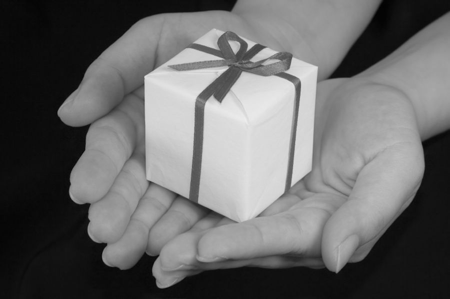Black and white photo of hands holding a small gift box