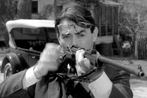 Black and white still from a movie showing a man with his glasses pushed up as he loads a gun and prepares to shoot