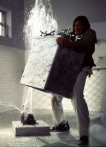 Still shot from a movie showing a man ripping a sink and cabinet unit from the ground in a bathroom with water shooting upward from the floor