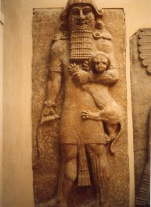 Photo of an ancient sculpture of a man holding a wild animal