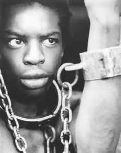 Black and white photo of a Black man with chains around his neck connecting to a chain wristband on a white arm