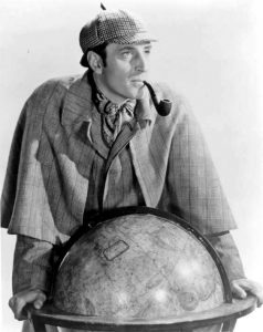 Black and white photo of a man leaning over a globe with a pipe in his mouth and a detective's cap on his head