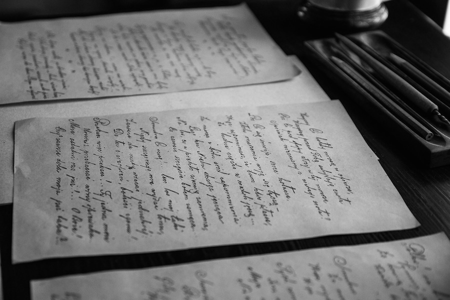 Black and white photo of old hand-written letters in script