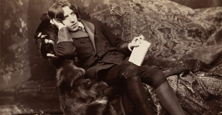 Portrait of Oscar Wilde lying back on a lavish couch covered in fur blankets