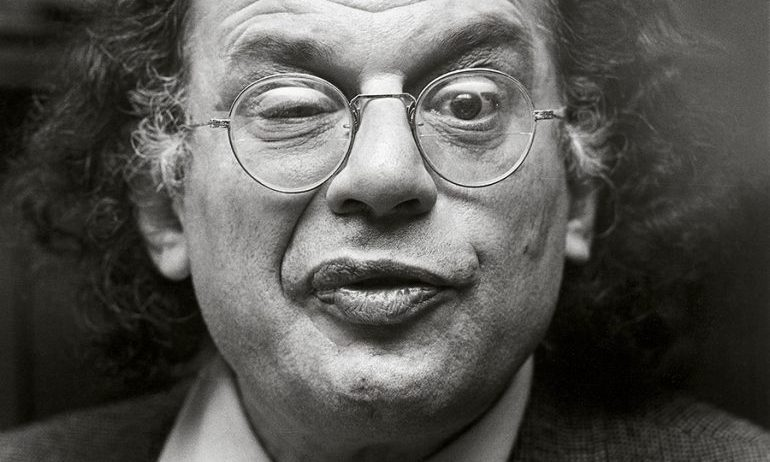 black and white photo of Allen Ginsberg wearing round glasses and making a silly face