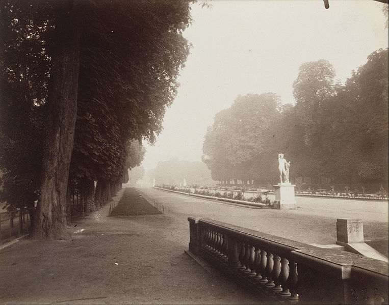 sepia photograph of a foggy promenade--there is a classical statue in center right of the photograph