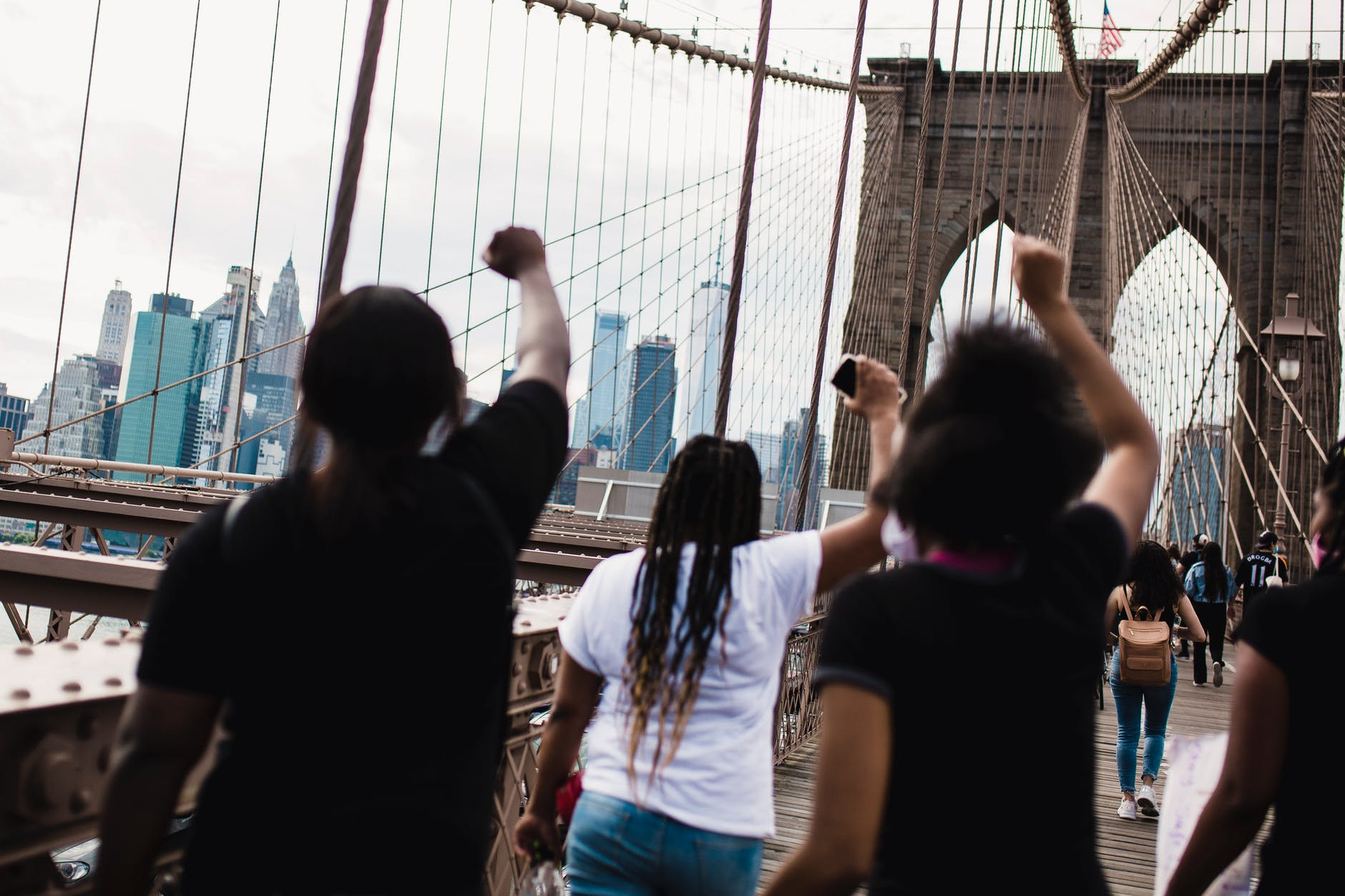 photograph of Black activists from behind with their fists raised as they march across the Brooklyn Bridge