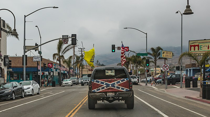 photograph of a pick up truck with a confederate flag on the tailgate. the truck is driving own a street--the background consists of an intersection and palm trees